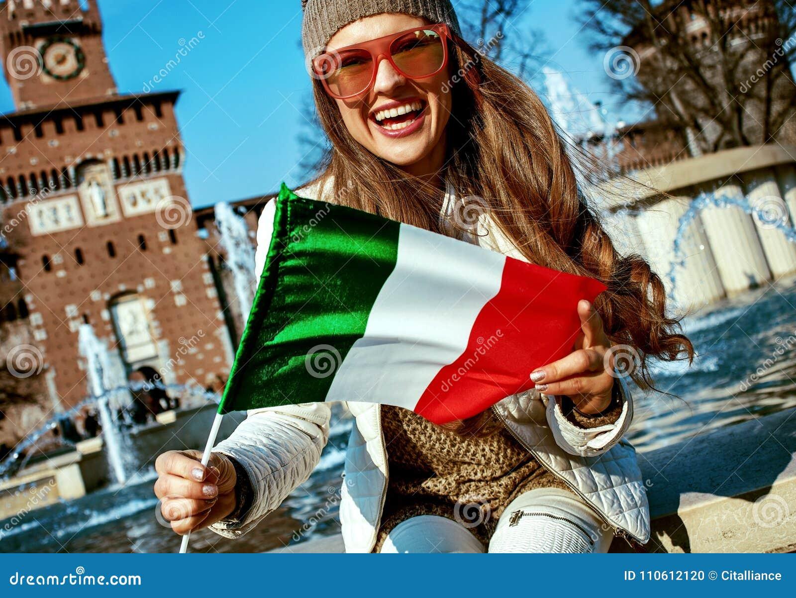 Turystyczna kobieta blisko Sforza kasztelu w Mediolan, Włochy seansu flaga
