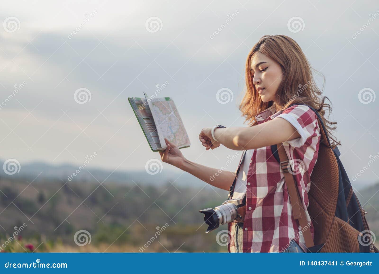 Turystyczna kobieta patrzeje lokacji mapę i wristwatch