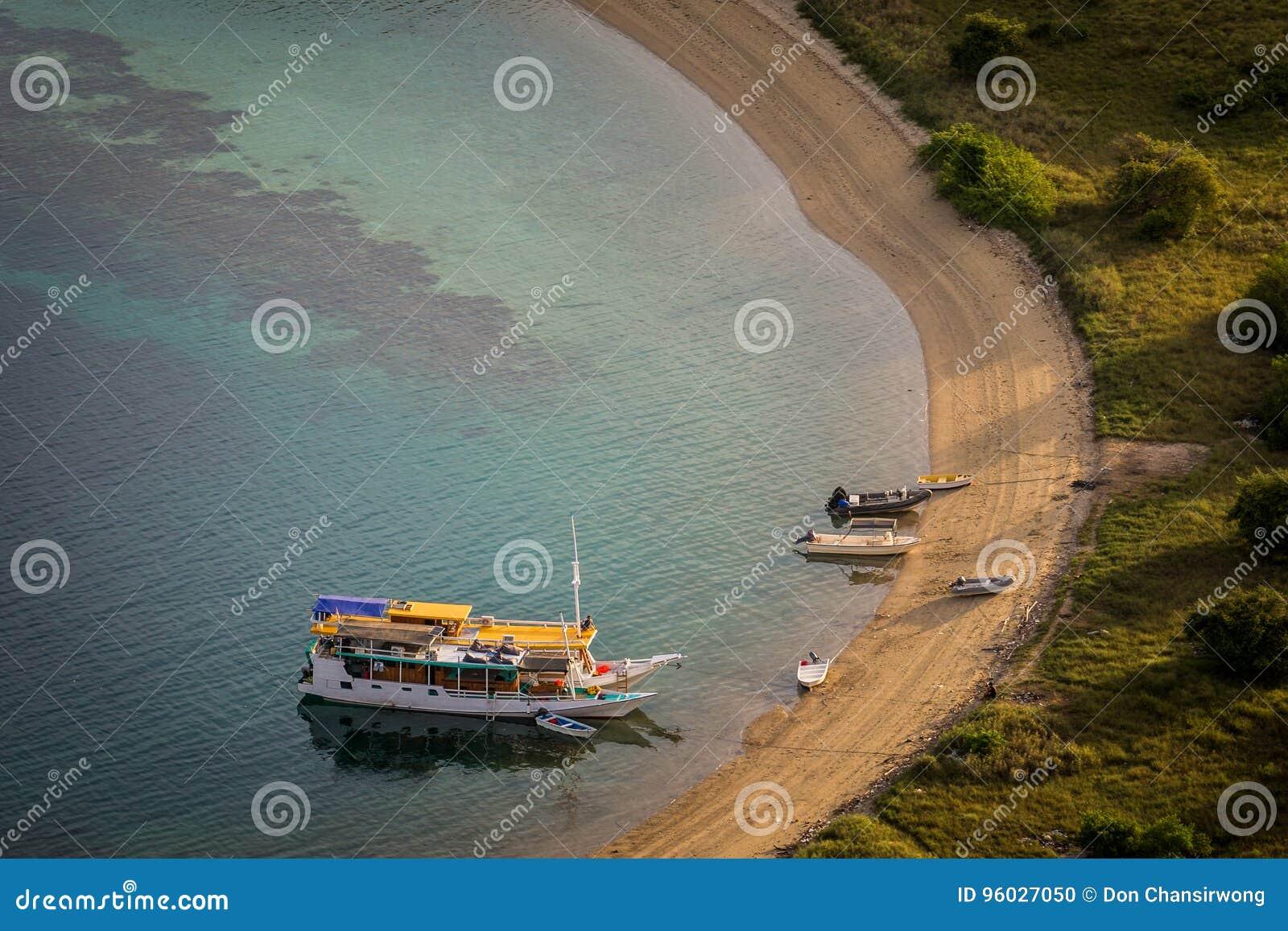 Turystyczne łodzie parkują przy pustą plażą