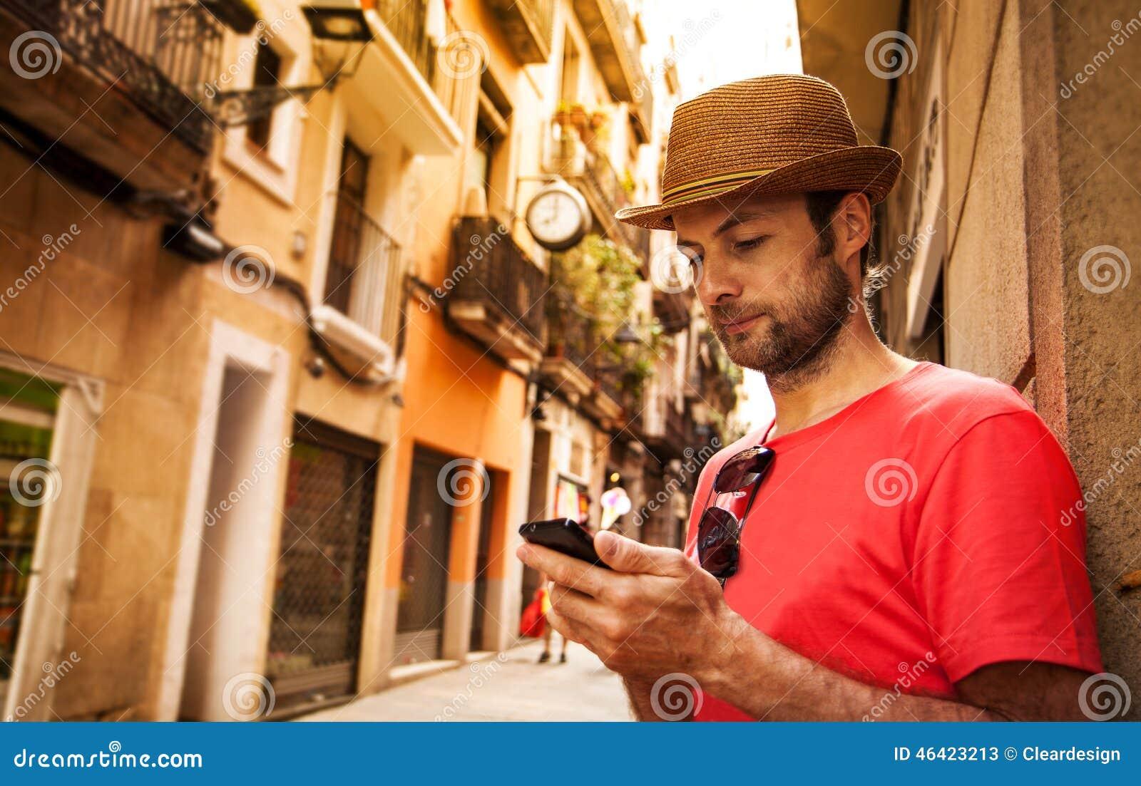 Turystyczny mężczyzna patrzeje telefon komórkowego - wakacje letni
