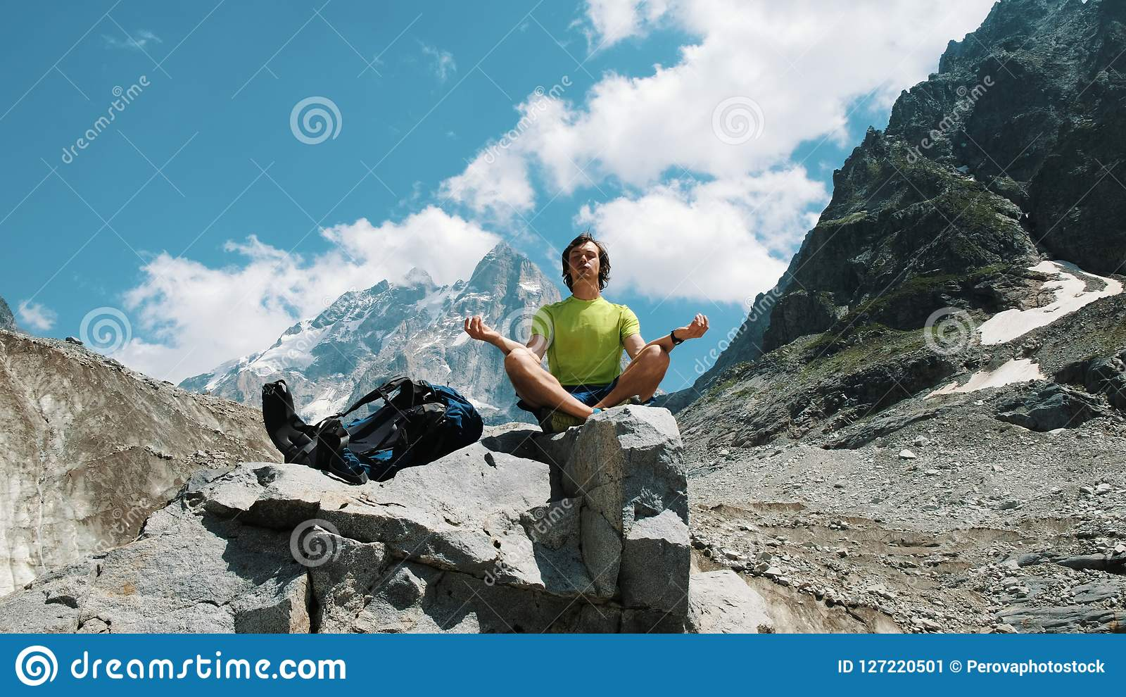 Turystyczny mężczyzna wycieczkowicz medytuje w górach siedzi na kamieniu, relaksuje i pacyfikuje w dzikim,