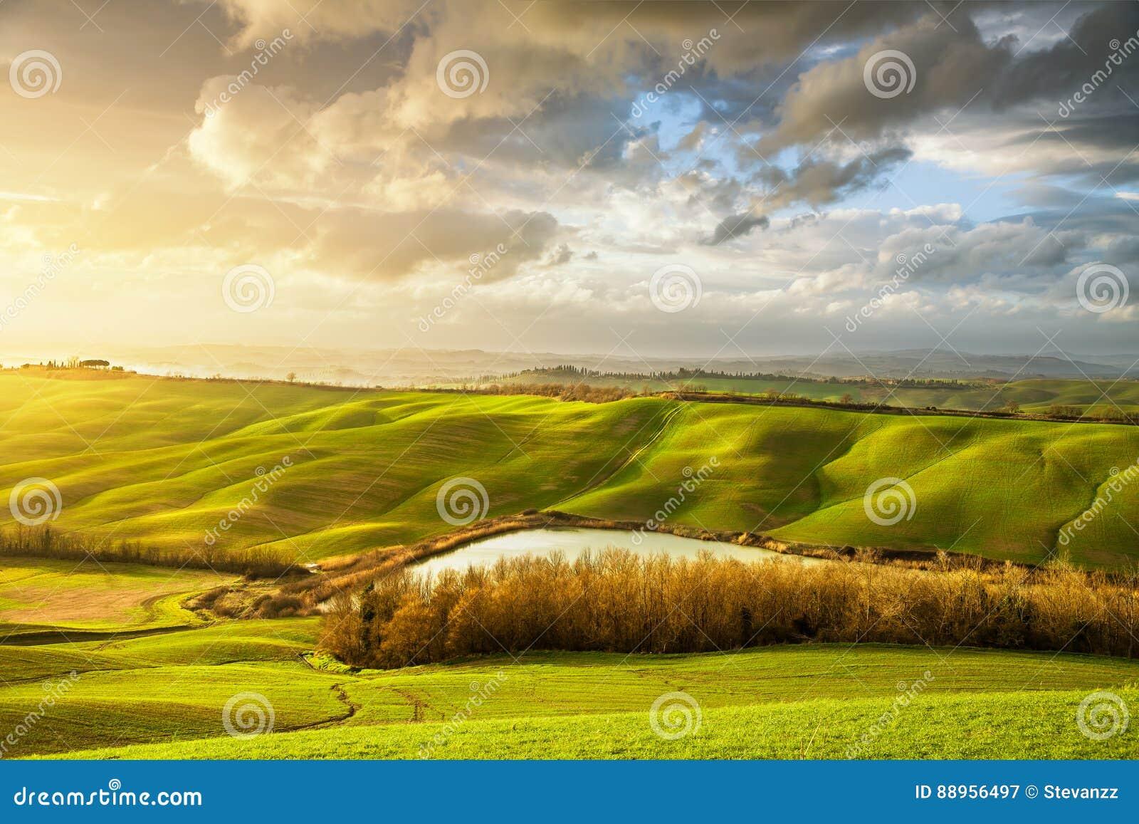 Tuscany mglista panorama przy zmierzchem, toczni wzgórza, jezioro, pola, m