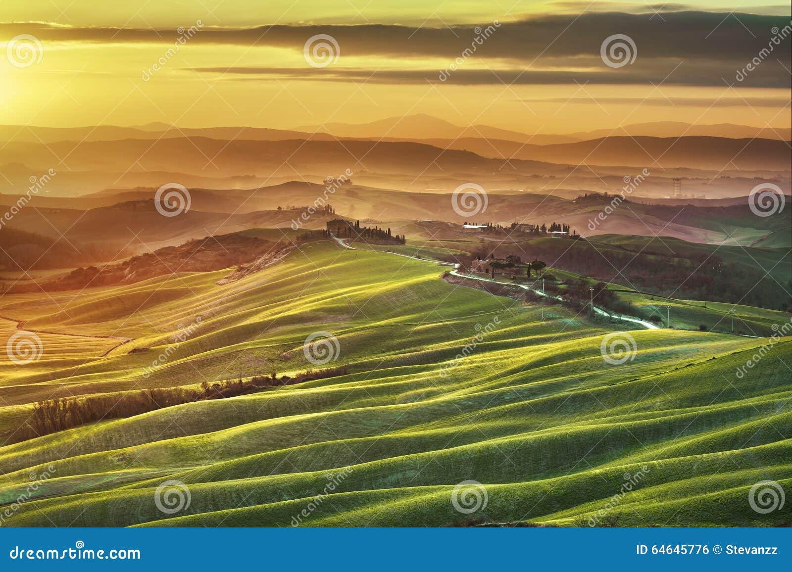 Tuscany spring, rolling hills on misty sunset. Rural landscape.