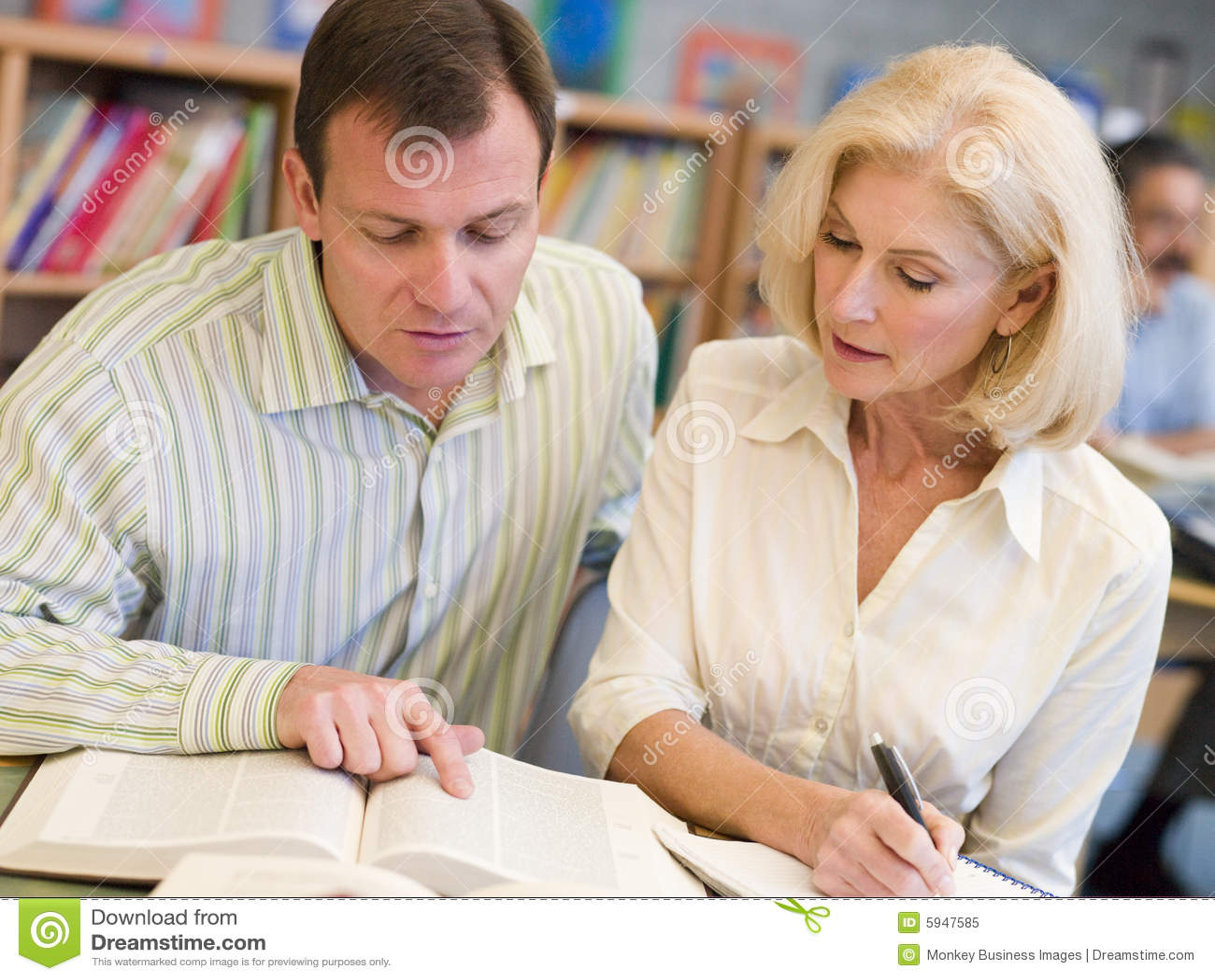 Tutor die Unterstützung des fälligen Kursteilnehmers in der Bibliothek