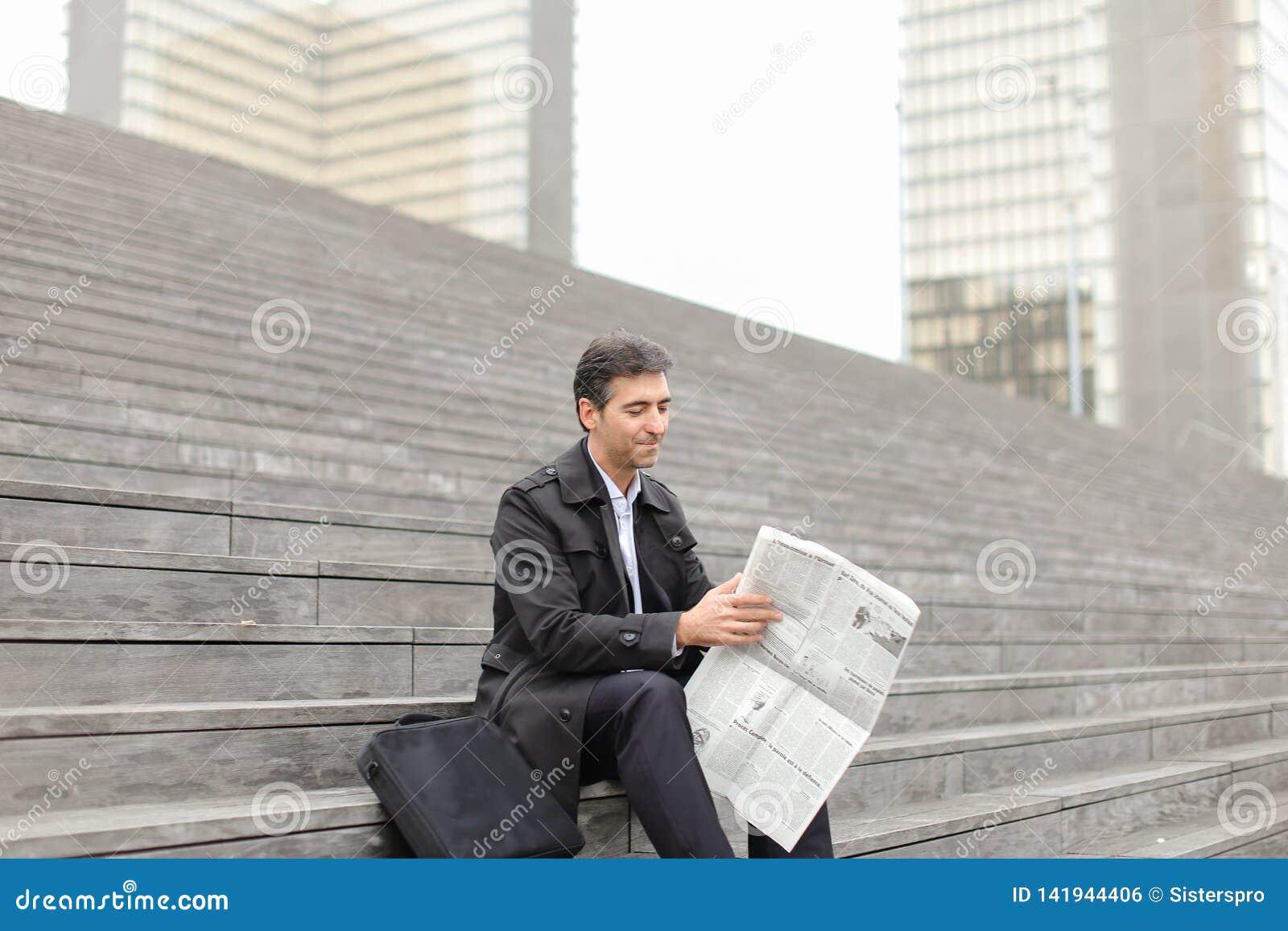 Tutor masculino do negócio que senta-se em escadas e que lê o jornal