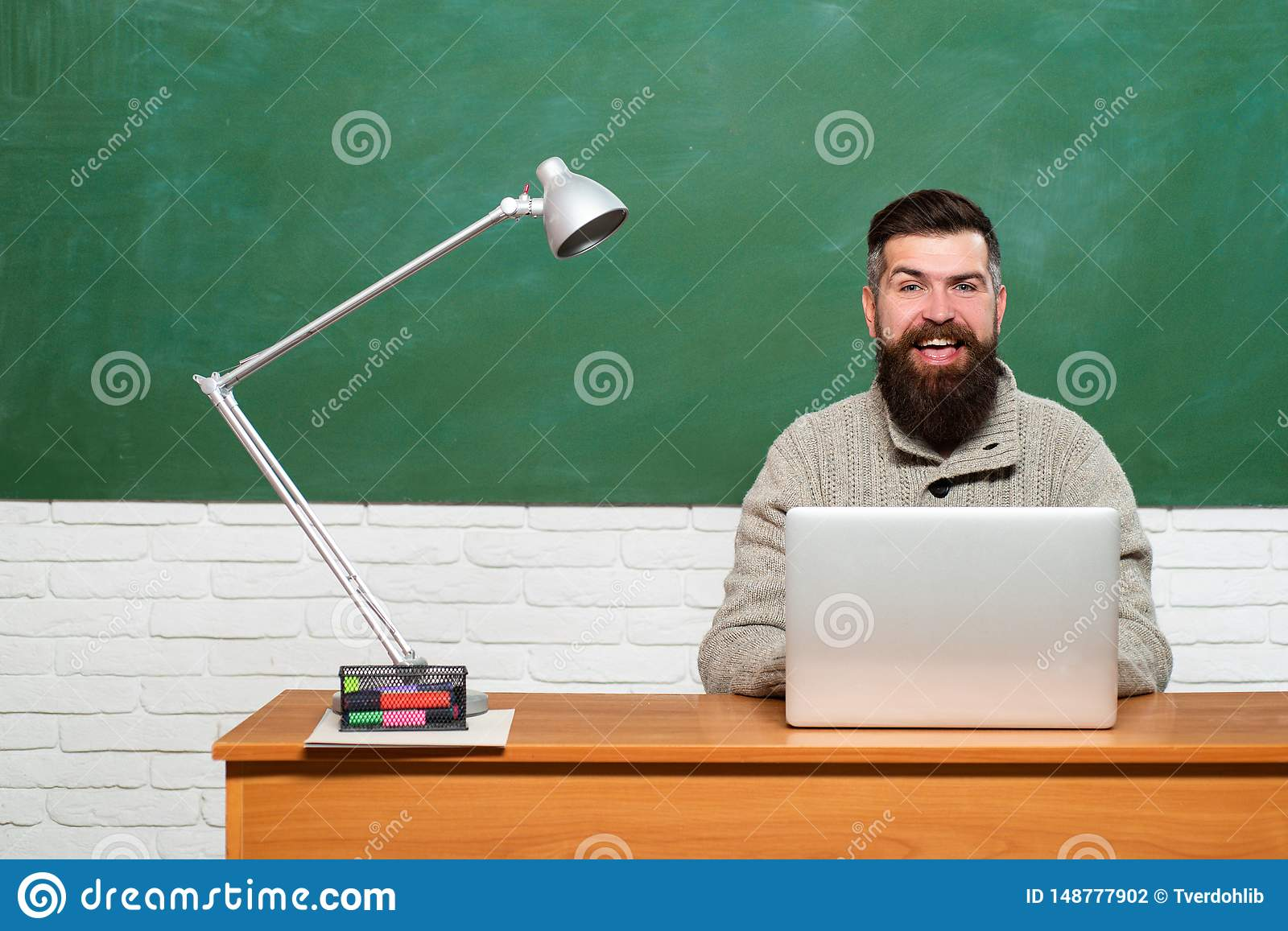 Tutor. Preparing for exam in college. Young teacher near chalkboard in school classroom. Science and education concept.