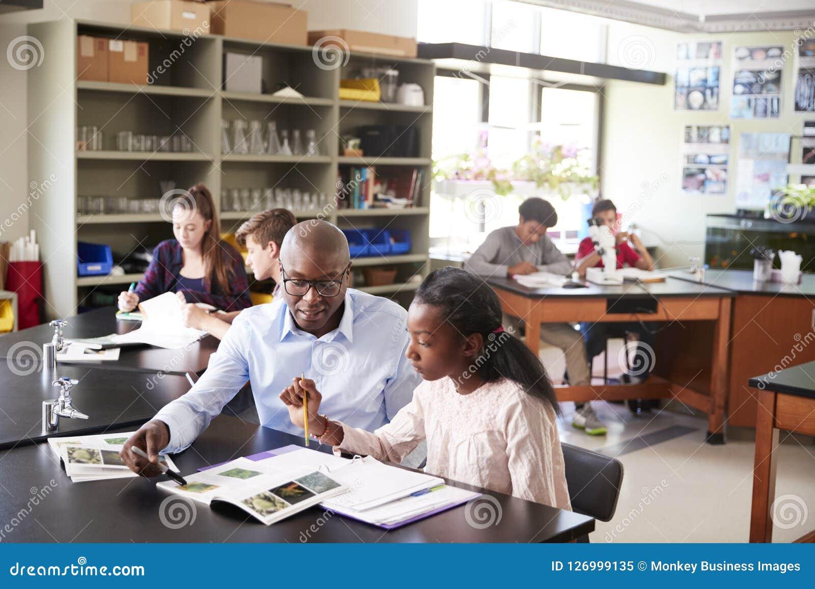 Tutor Sitting At Desk da High School com estudante fêmea In Biology Class