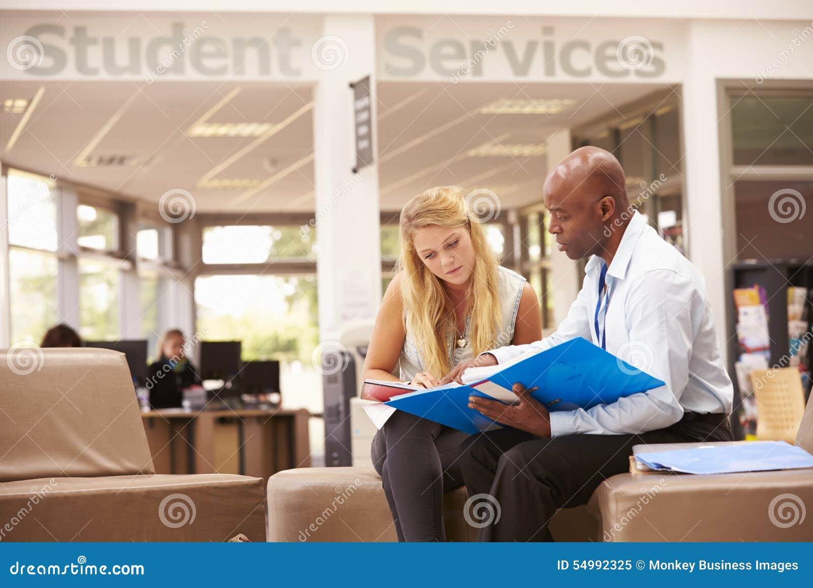 Tutor To Discuss Work de Having Meeting With da estudante universitário