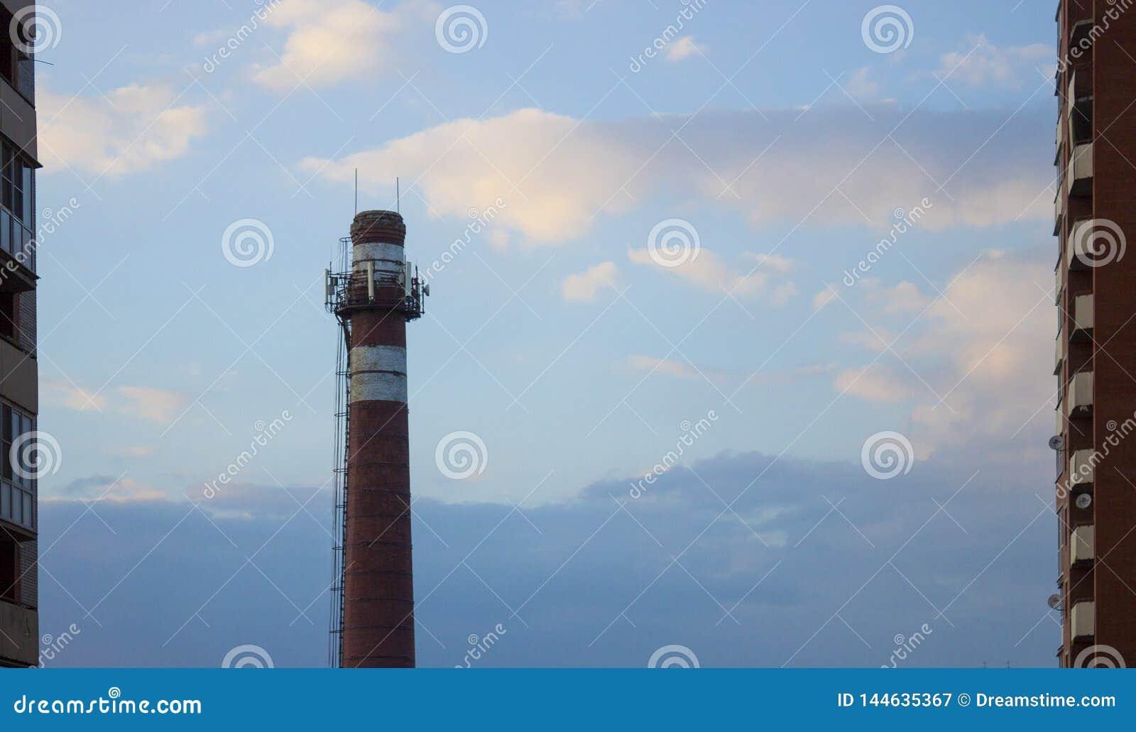 Tuyau de brique de la chaufferie sur le ciel bleu entre les gratte-ciel