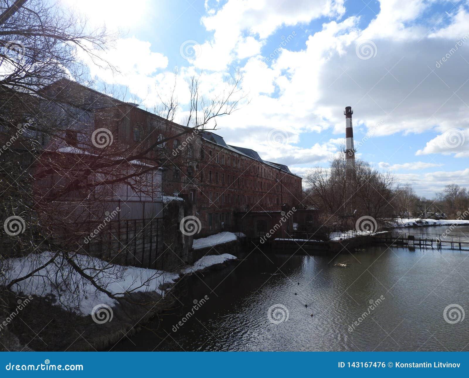 Tuyau industriel vieille de brique rouge et blanche sur le fond de ciel bleu La vieille image du concept d industrie Écologie, re