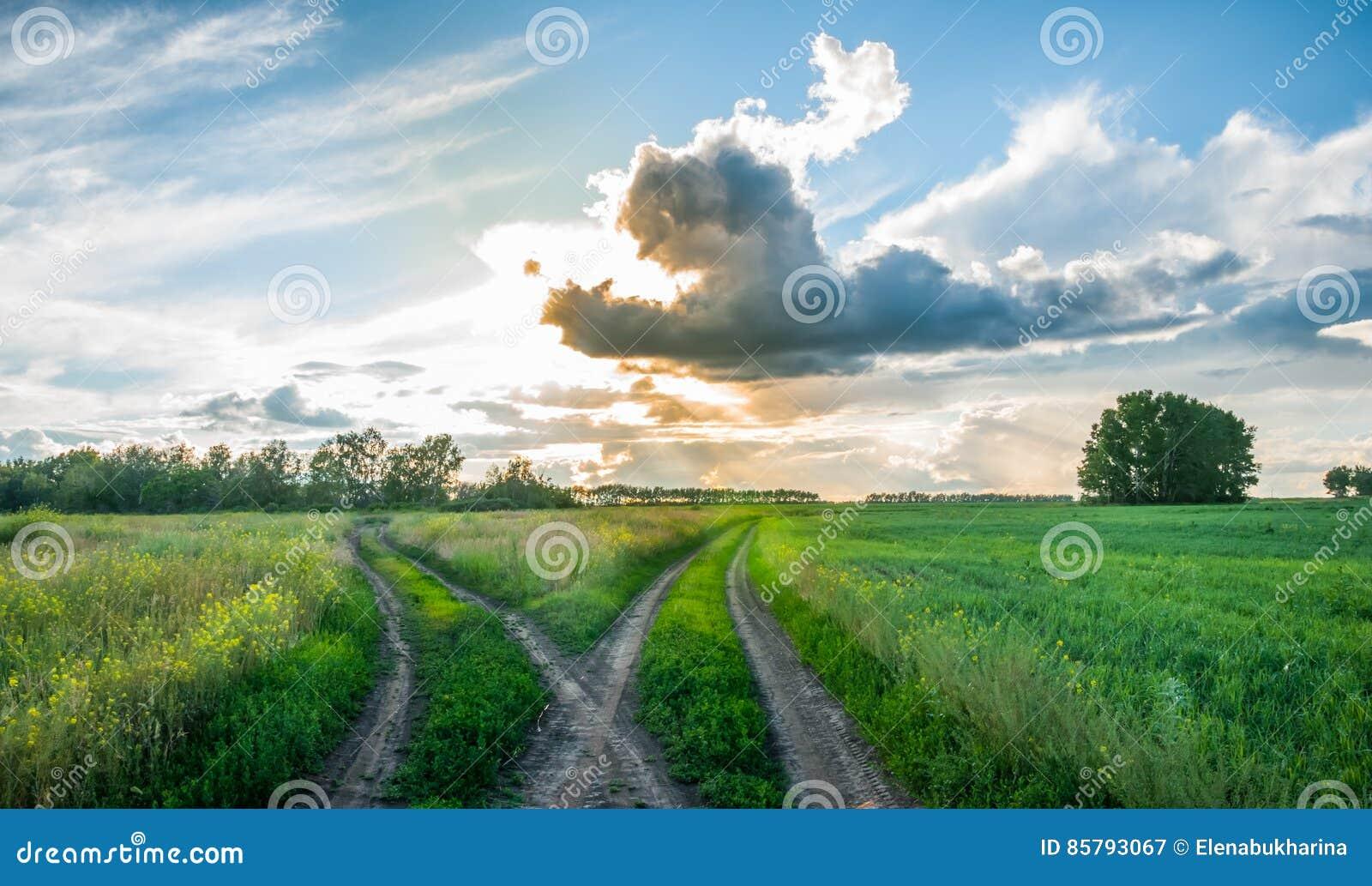 Tvärgator i fältet på solnedgången Kluven landsväg beautiful clouds lantlig liggande
