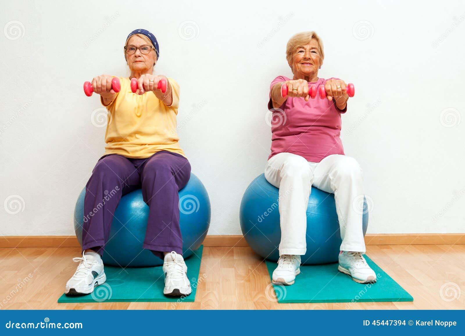 Två äldre kvinnor som gör muskeln, övar med vikter i idrottshall