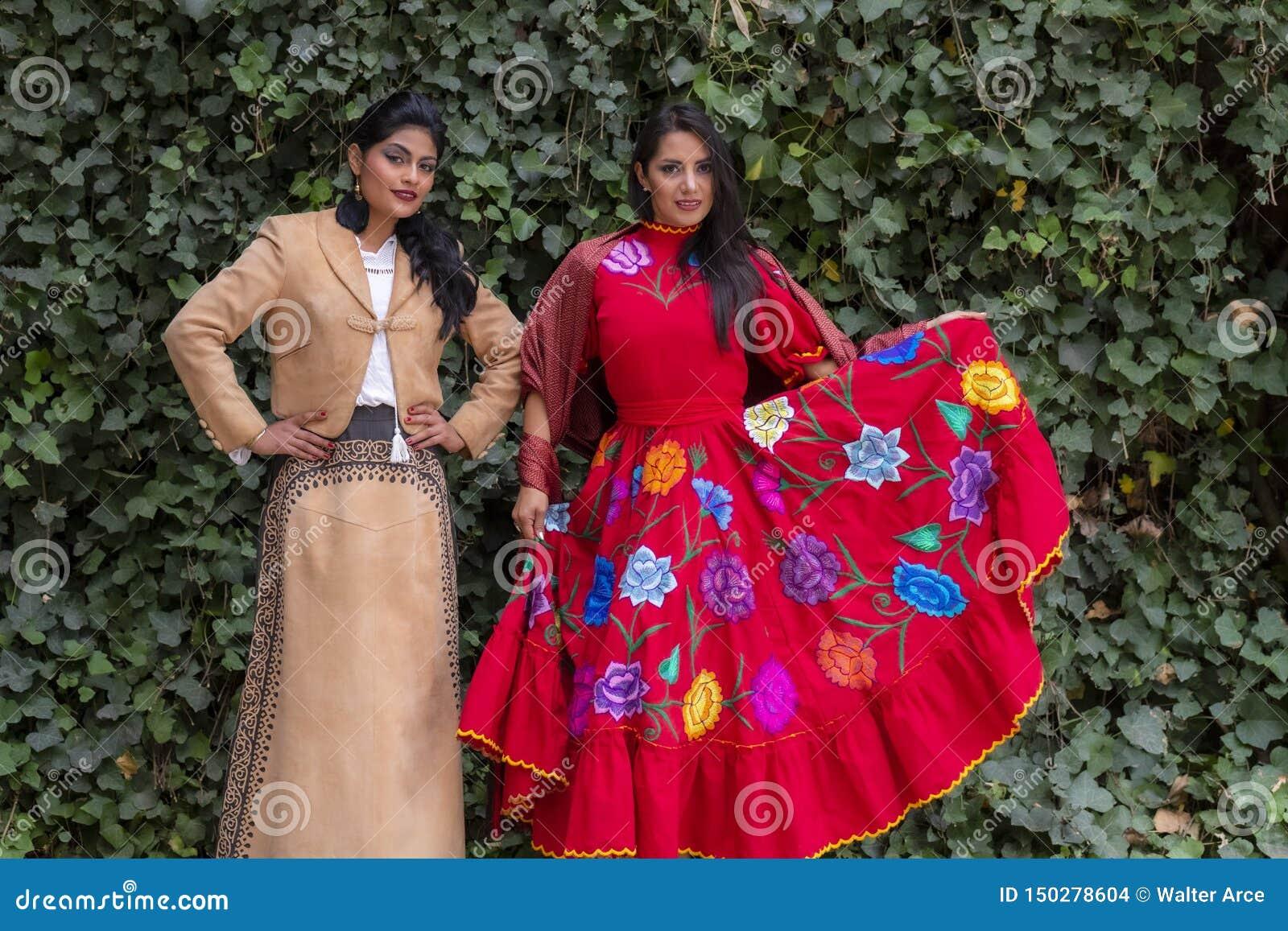 Två älskvärda latinamerikanska brunettmodeller poserar det fria på en mexicansk ranch