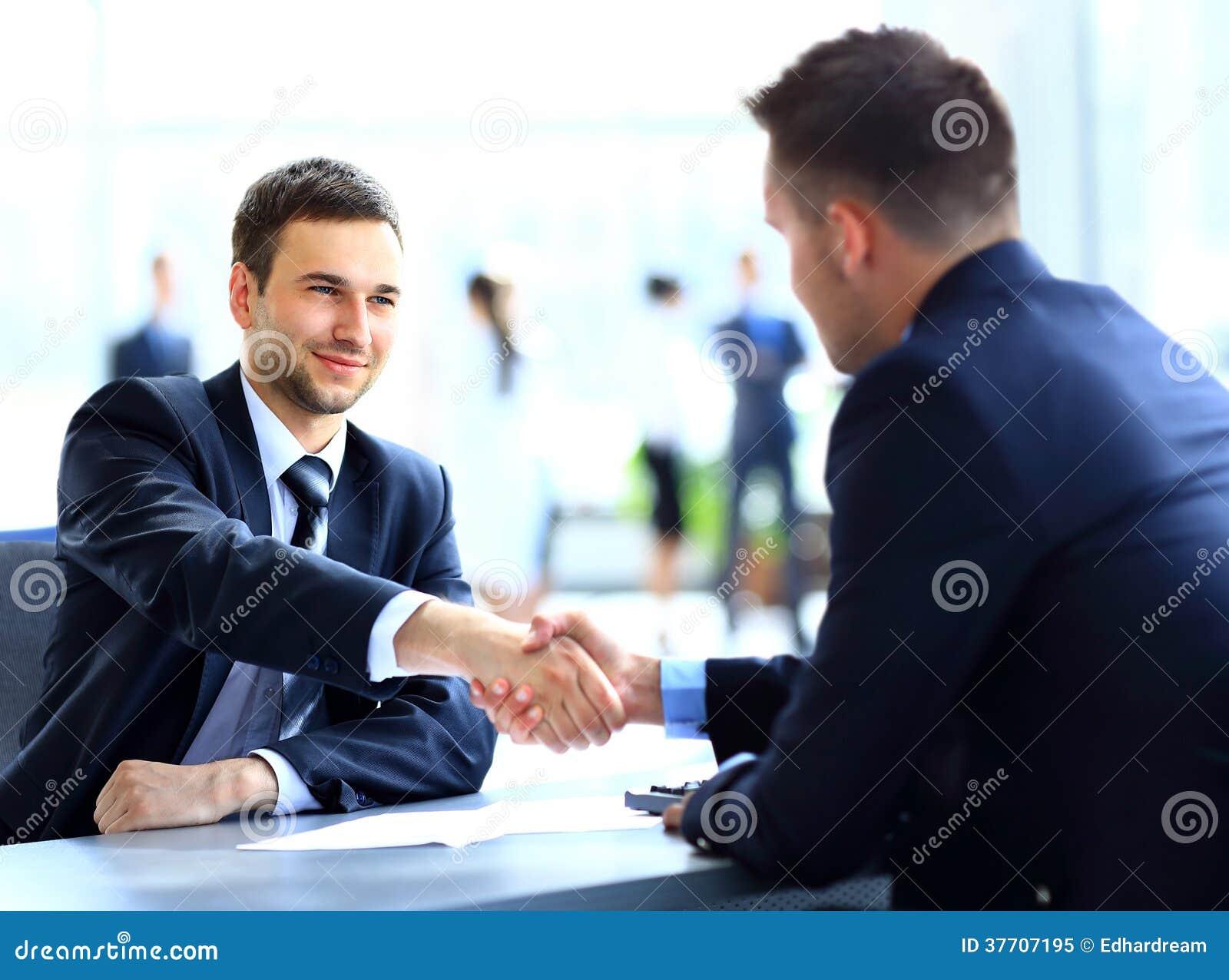 Två affärskollegor som skakar händer under
