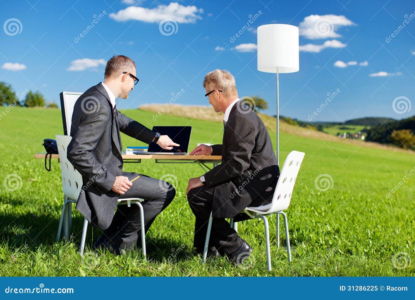 Två affärsmän som arbetar i natur