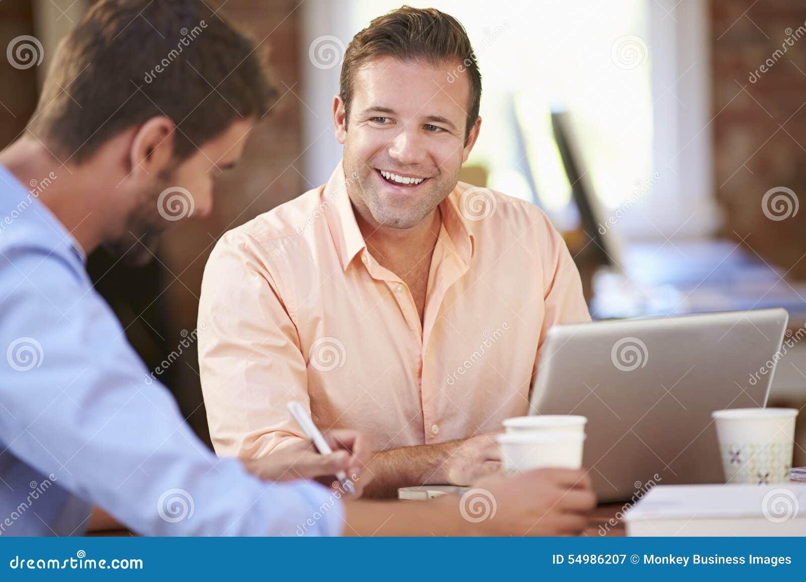 Två affärsmän som tillsammans arbetar på skrivbordet