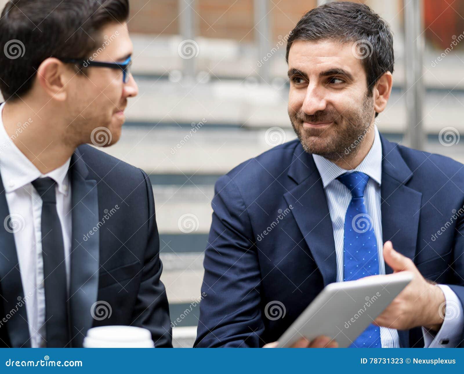 Två affärsmän som utomhus talar