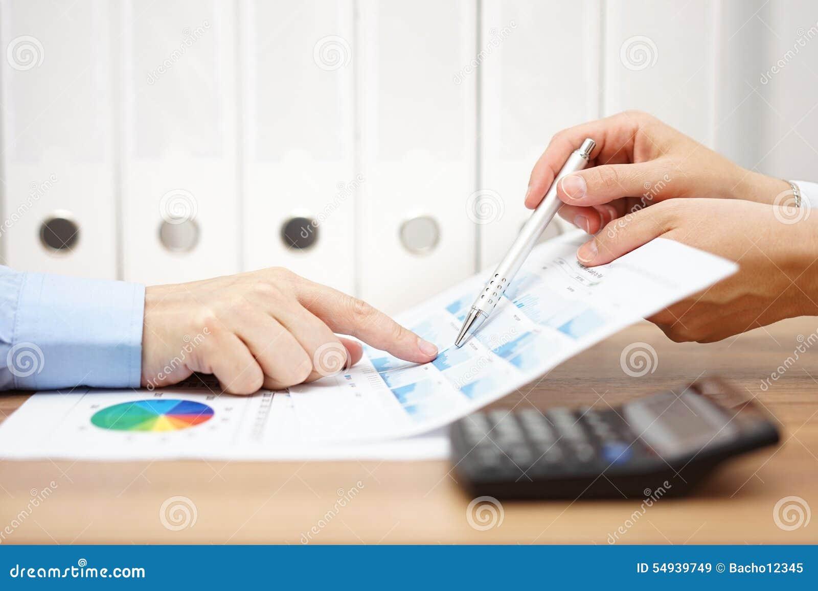 Två affärspersoner på möte analyserar den finansiella rapporten och di