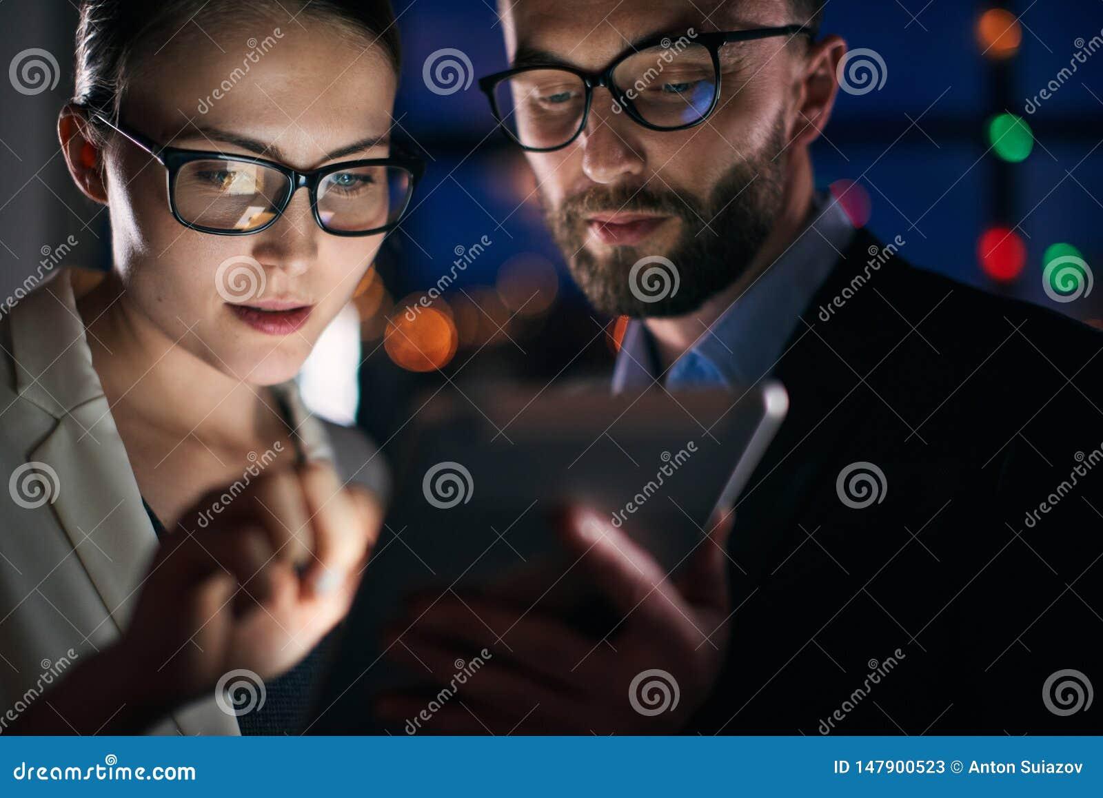 Två affärspersoner som arbetar på minnestavlan på natten