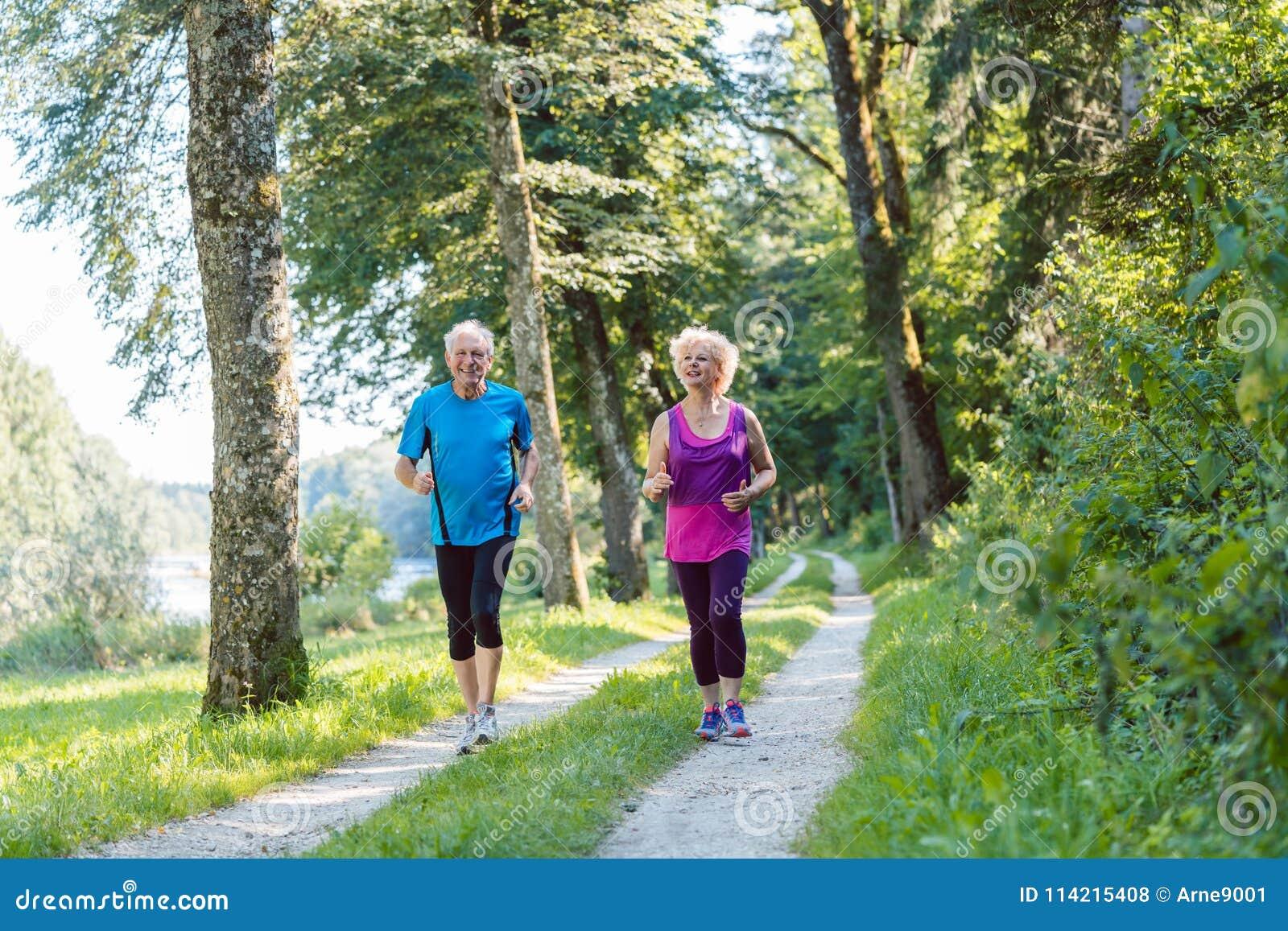 Två aktiva pensionärer med en sund livsstil som ler medan joggin