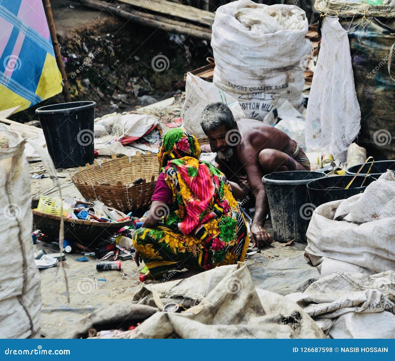 Två arbetare arbetar runt om ett ställe i Bangladesh det unika fotoet