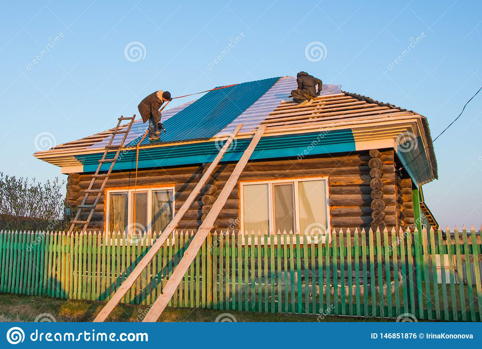Två arbetare täcker taket av ett lantligt hus med metalltegelplattor