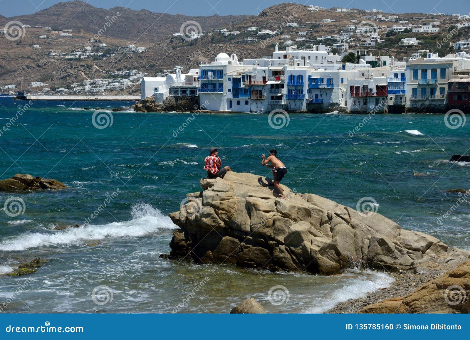 Två asiatic grabbar på vaggar i mitt av havet, ett skjuta foto, annat som en modell Den lilla Venedig