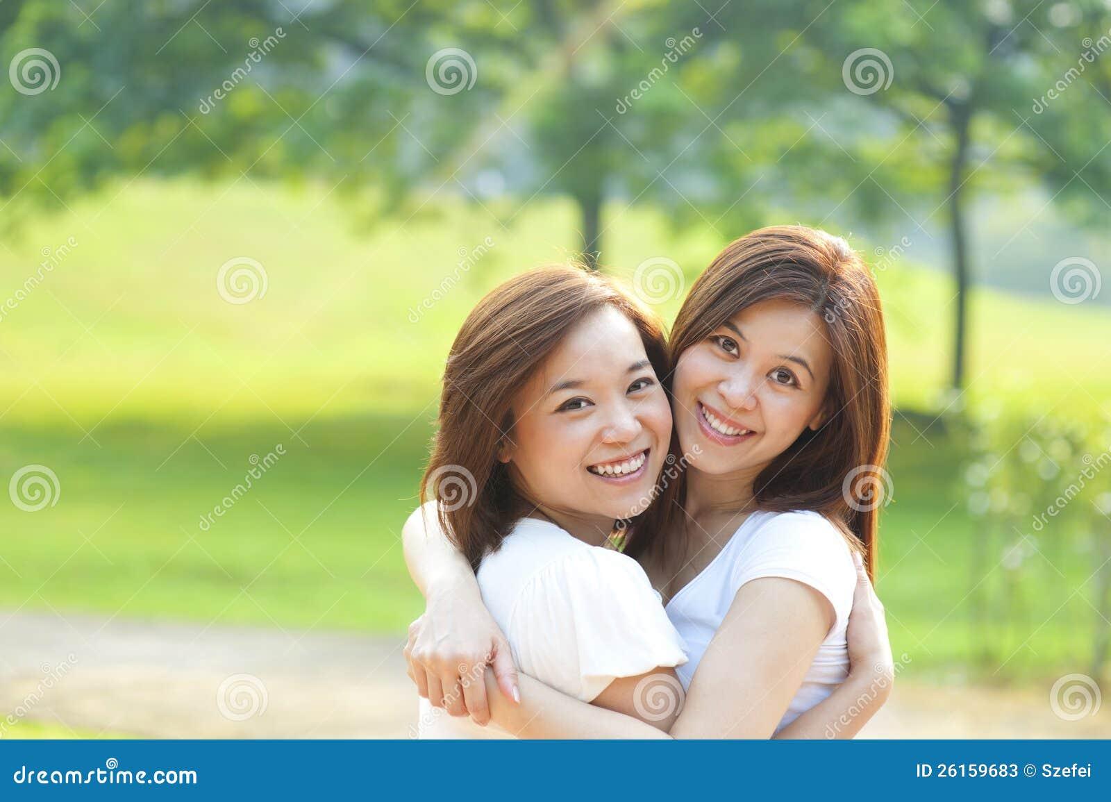 Två asiatiska flickor som har gyckel