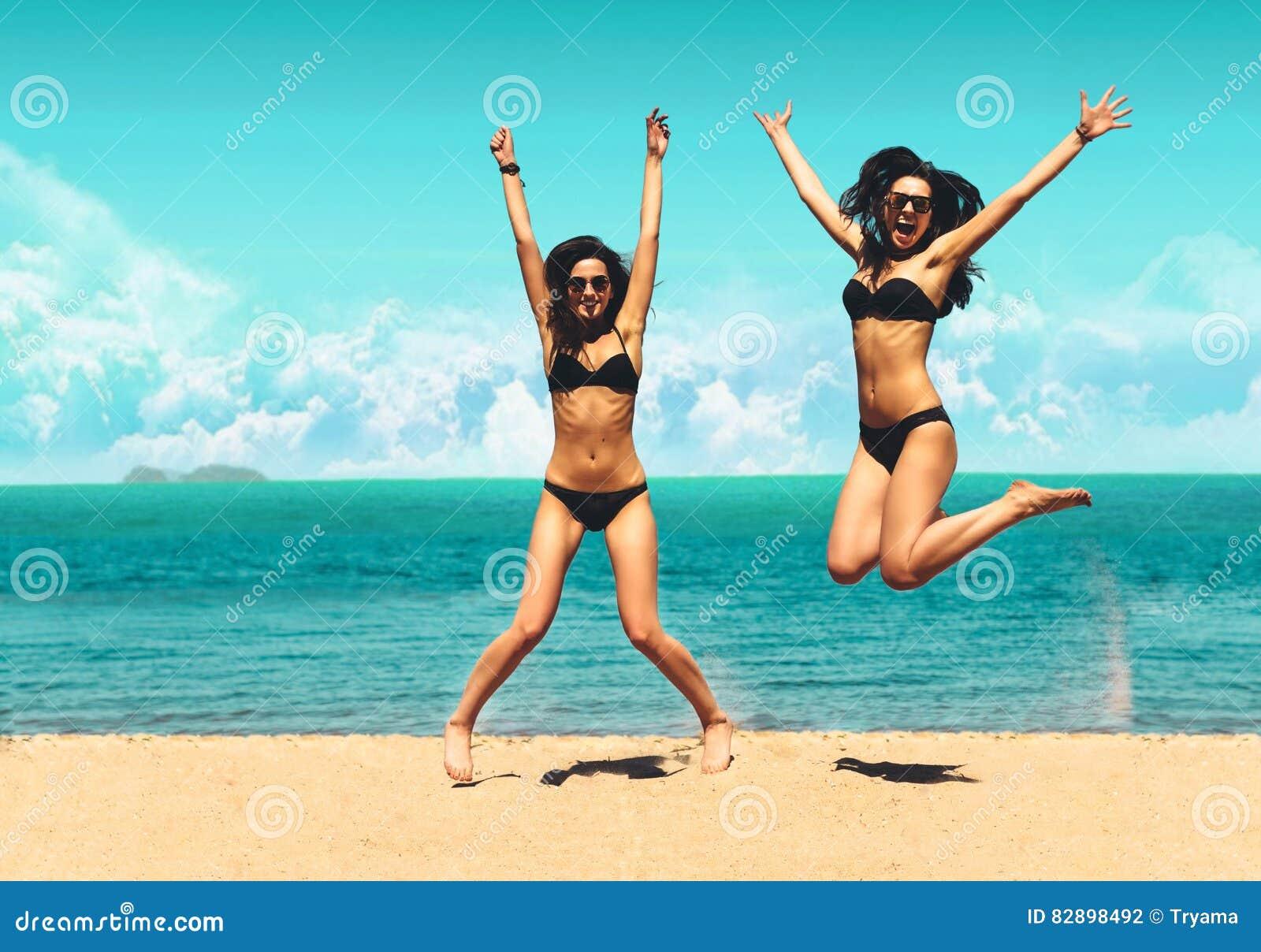 Två attraktiva flickor i bikinier som hoppar på stranden Bästa vän som har gyckel, livsstil för ferie för sommarsemester Lyckligt