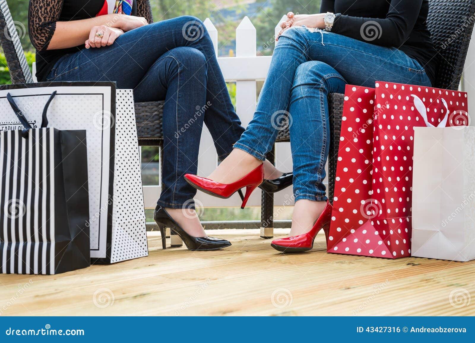 Två attraktiva unga kvinnliga vänner som tycker om ett avbrott efter lyckad shopping