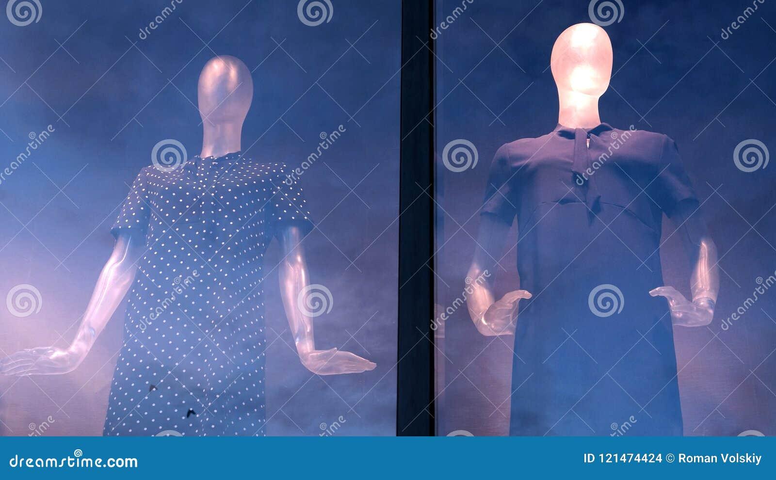 Två attrapper på gatan shoppar fönsterblick i olika riktningar Reflexion av morgon- eller aftonhimlen på exponeringsglaset double
