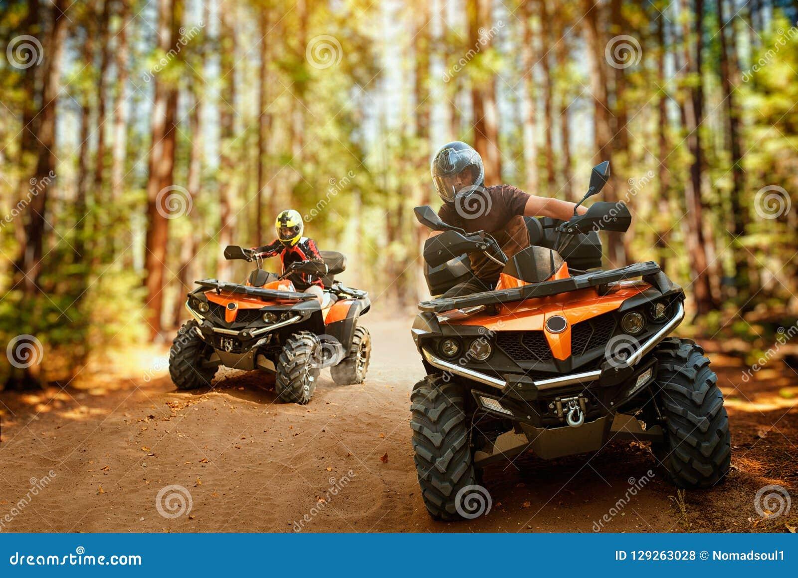 Två atvryttare, hastighetslopp i skog, främre sikt