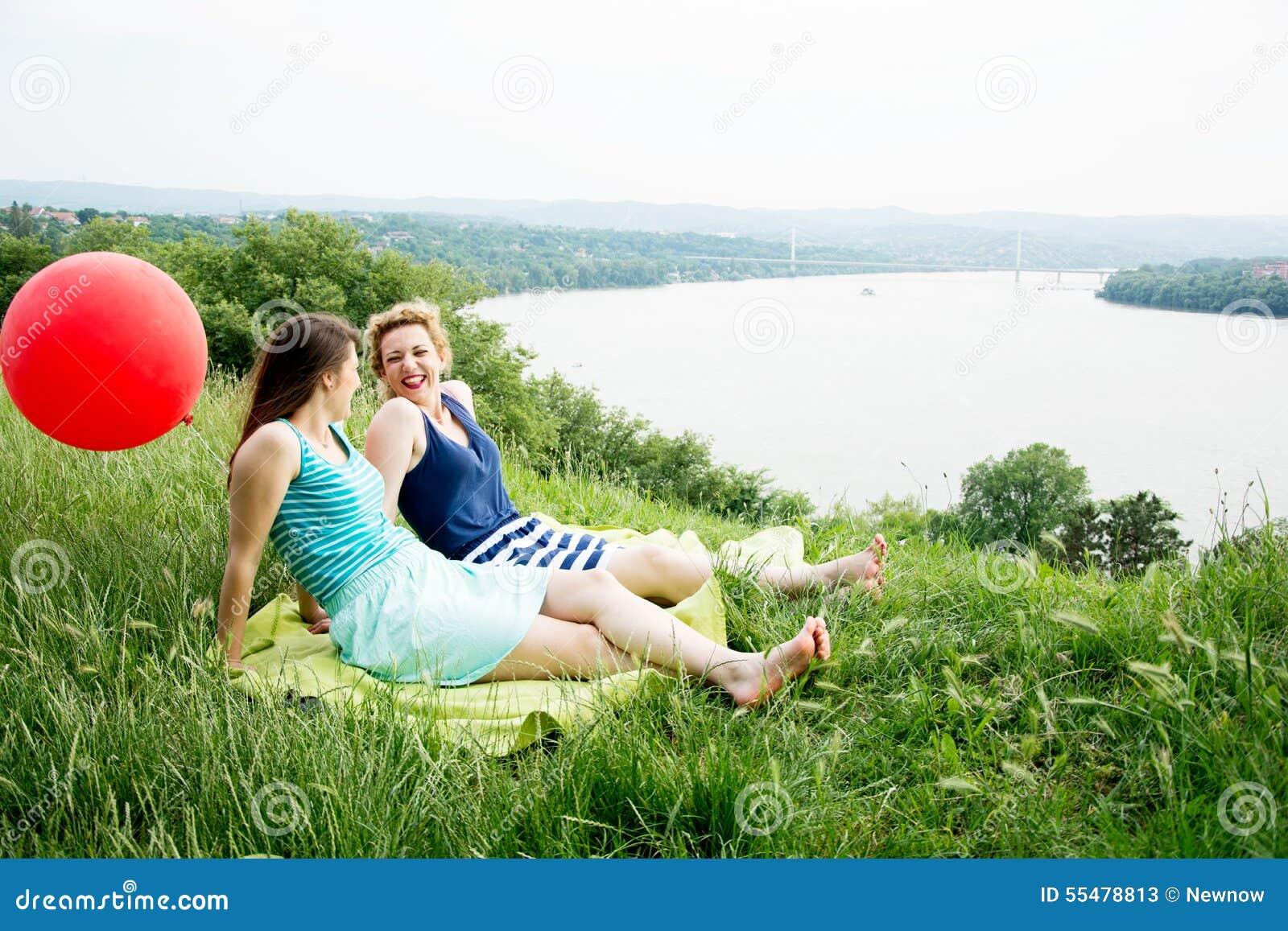 Två bästa flickavänner som sitter på gräset