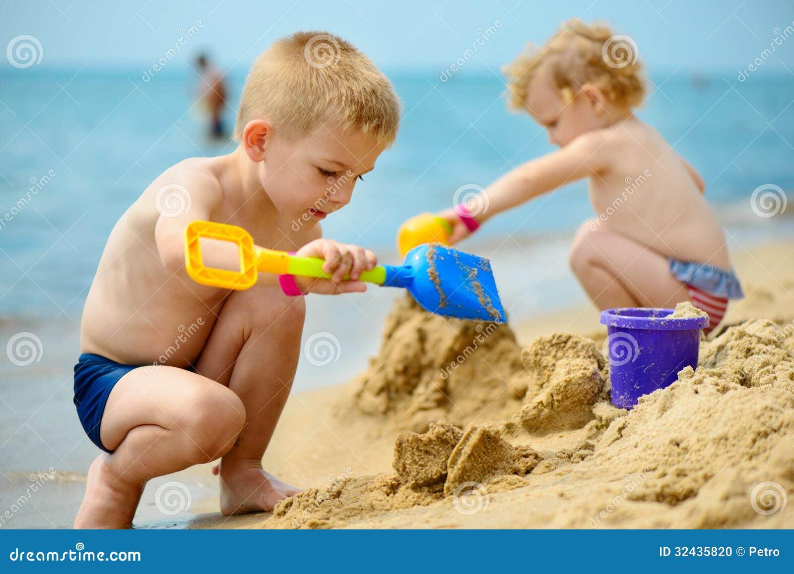 Två barn som spelar med sand på havstranden