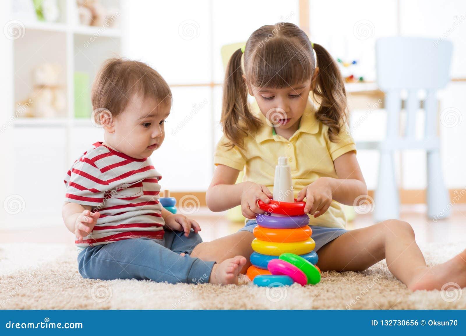 Två barn tillsammans Storasystern hjälper det mer ung för att montera leksakpyramiden