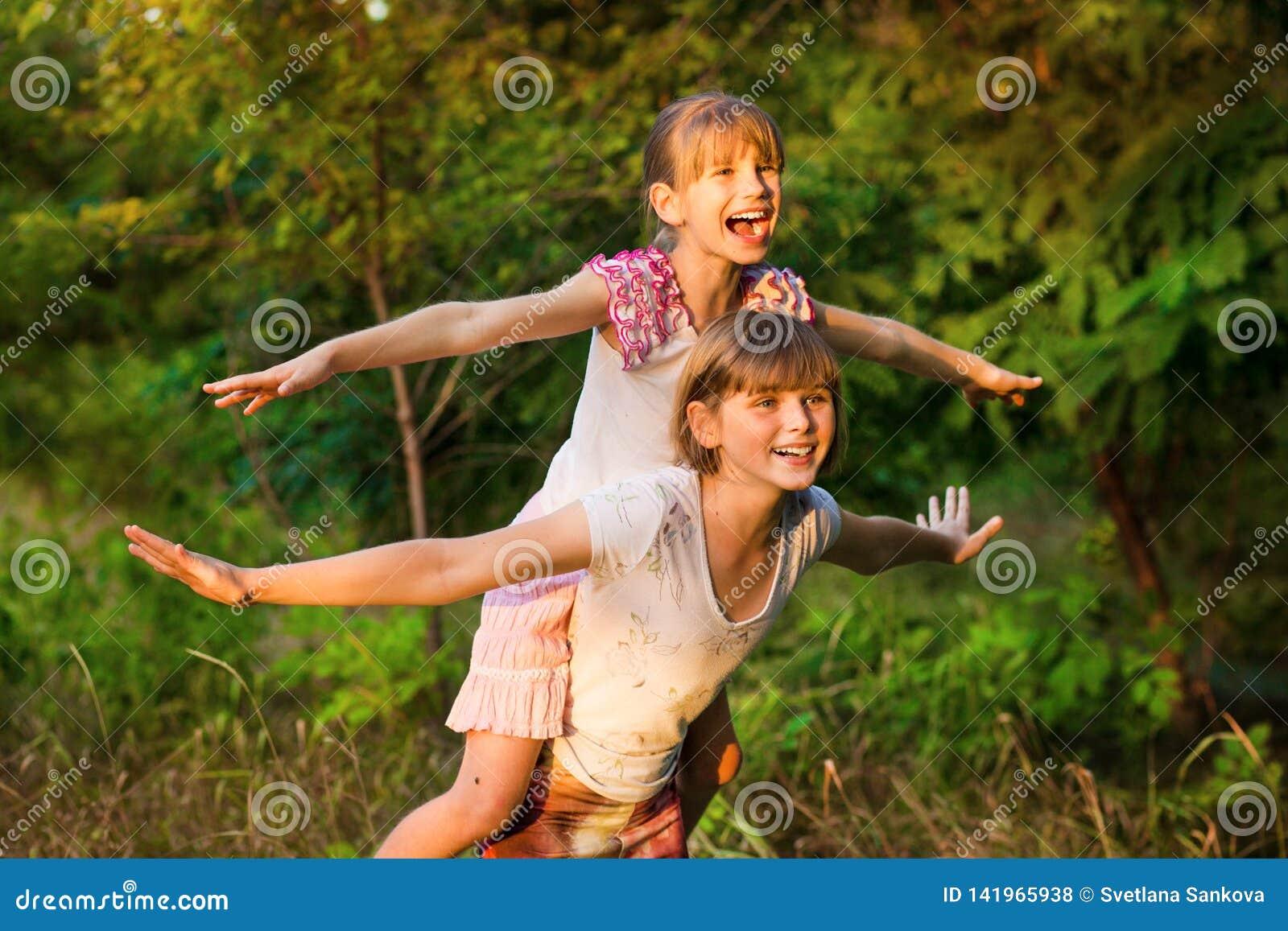 Två barnflickor som tillsammans spelar Systrar spelar superheroen Lyckliga ungar som har gyckel, att le och att krama