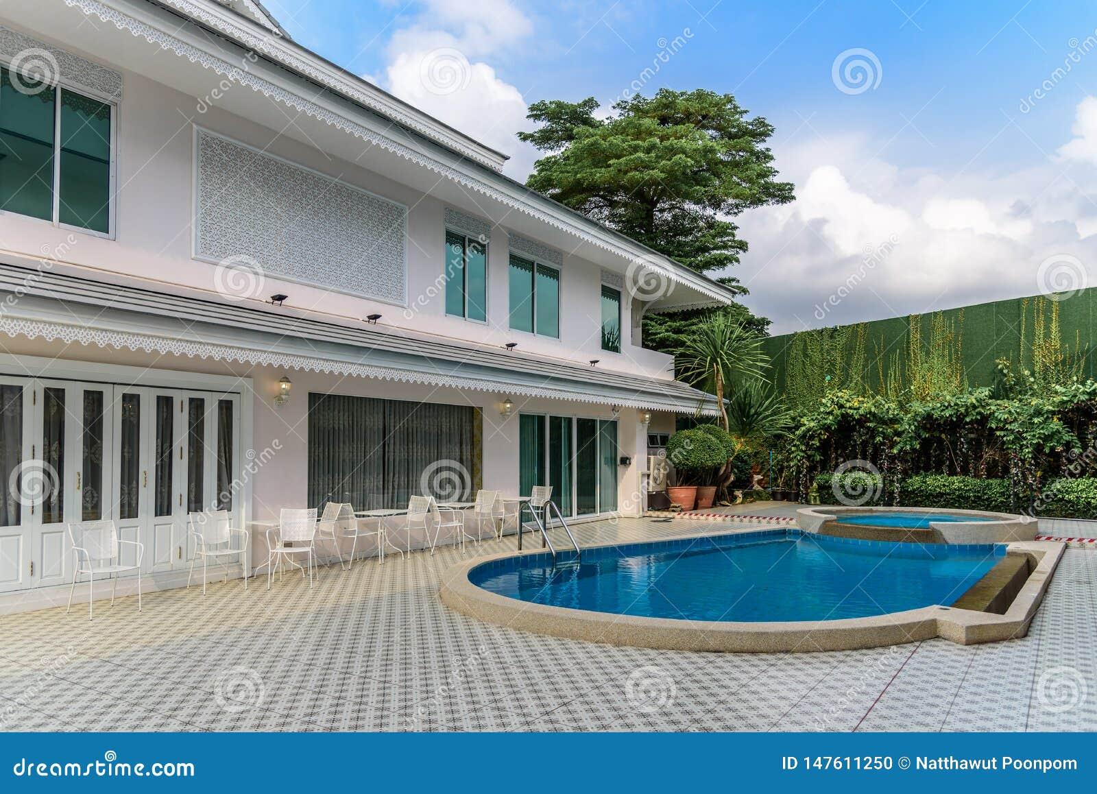 Två-berättelse hus med staketet och simbassängen