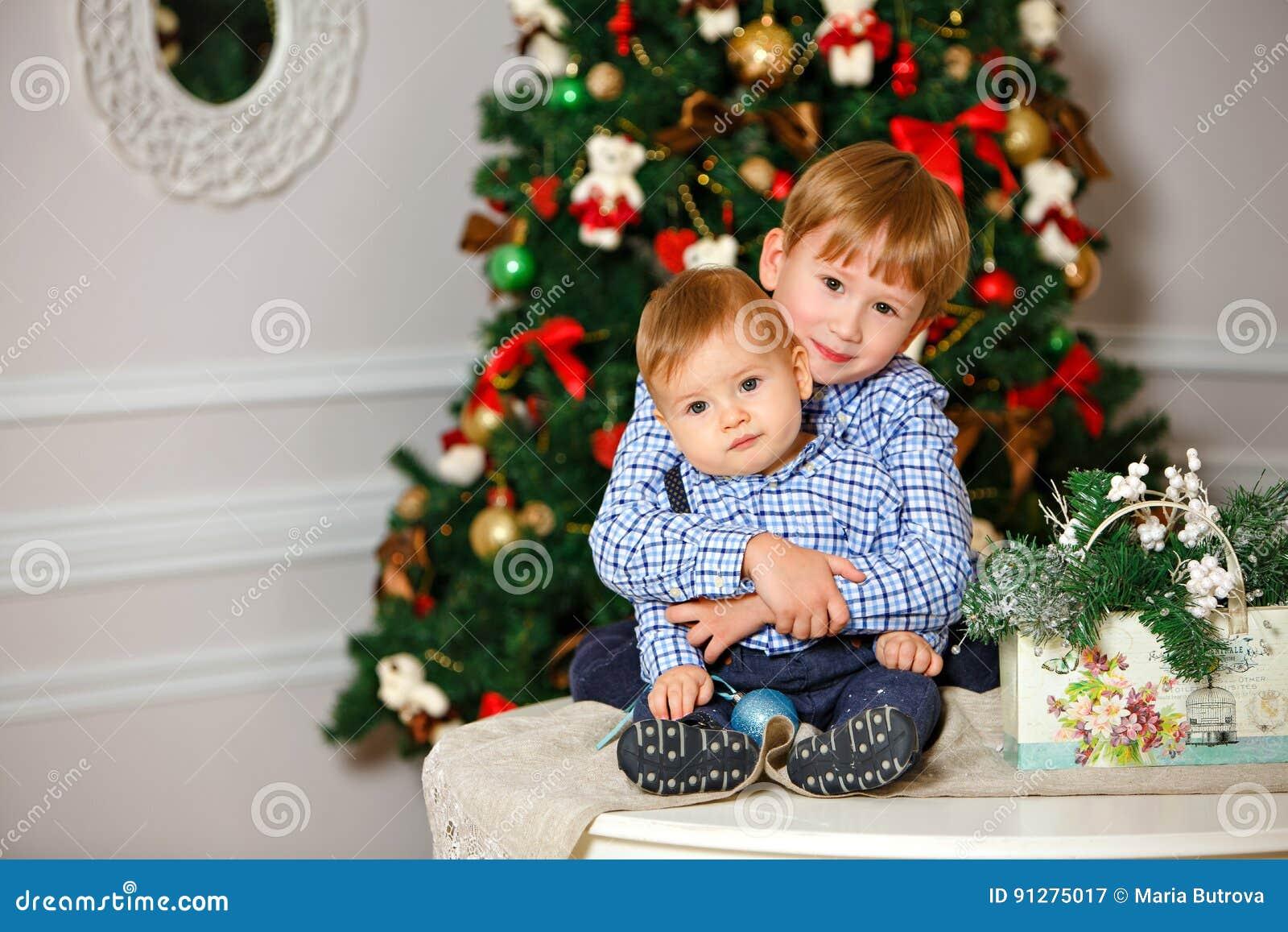 Två bröder i blå skjorta som ler och kramar på jul