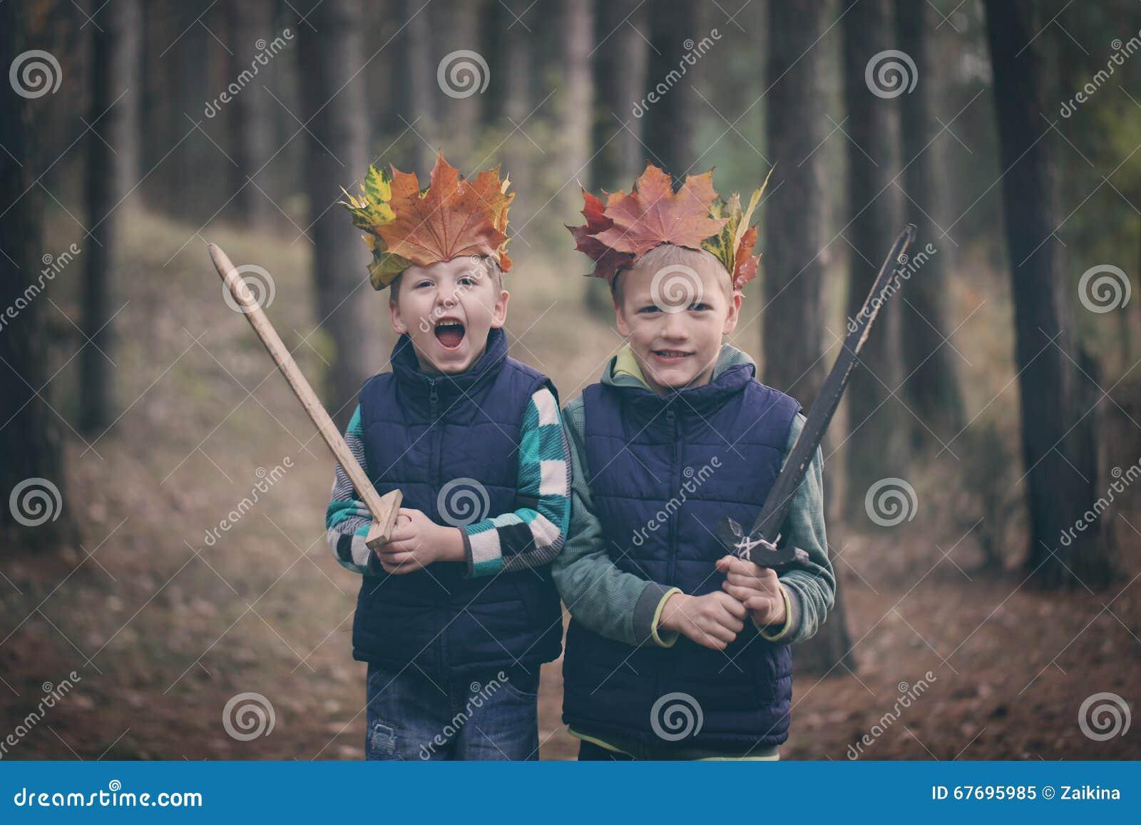 Två bröder som kelar i en skog på höstdag Små ungar hu