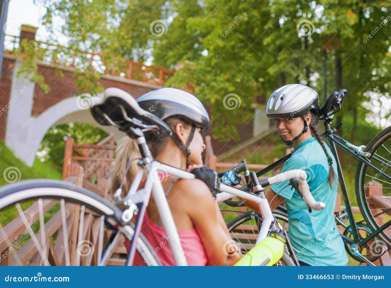 Två Caucasian idrottskvinnor utarbetar med cyklar