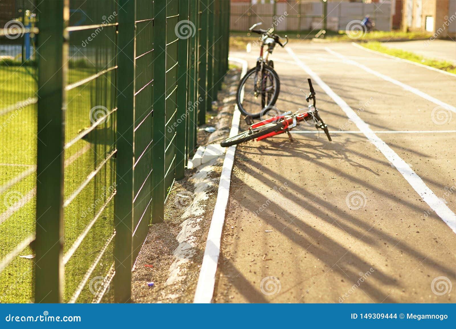 Två cyklar är på asfaltvägen av stadion Raster av det gröna staketet på bakgrunden av gräsmattafältet