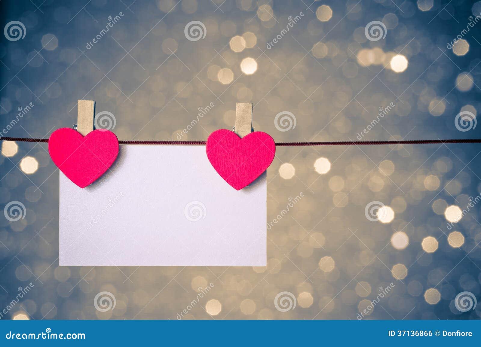 Två dekorativa röda hjärtor med hälsningkortet som hänger på blå och guld- ljus bokehbakgrund, begrepp av valentindagen