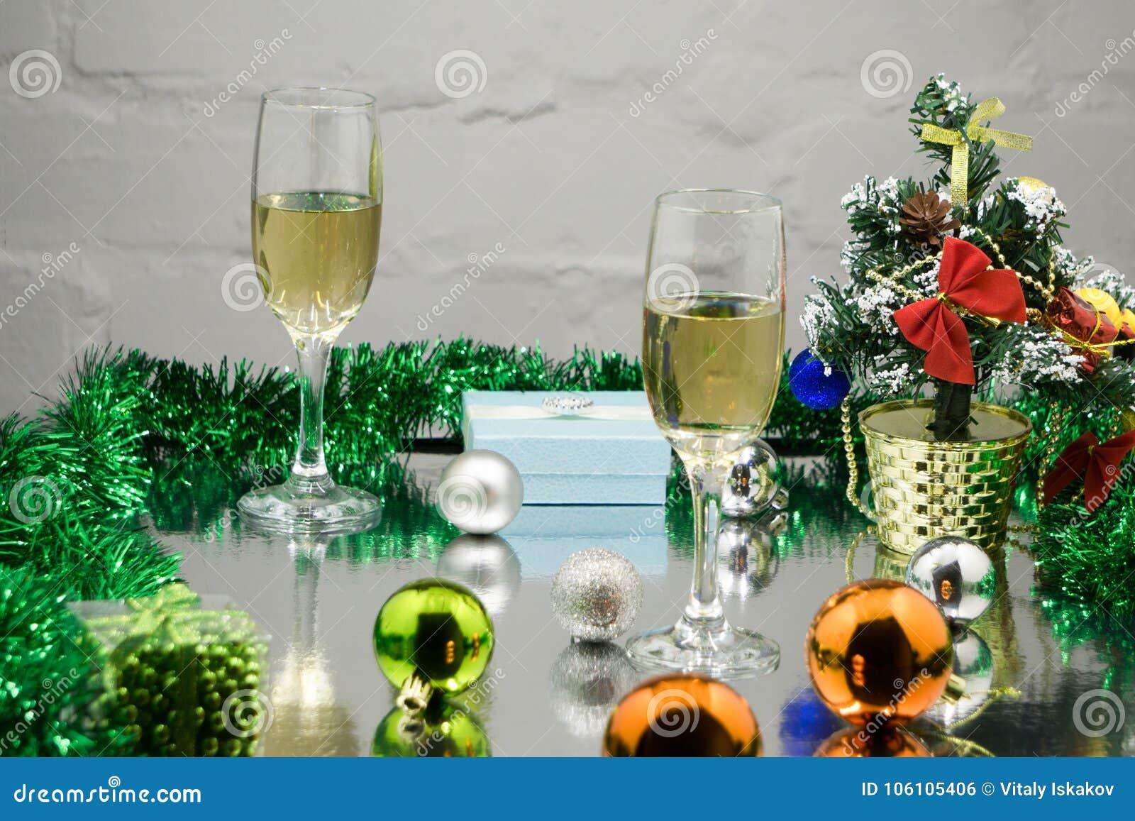 Två exponeringsglas av champagne med julgåva och julbollar