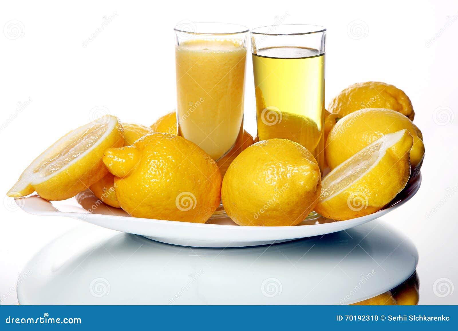 Två exponeringsglas av citronjuice och smoothies near nya citroner