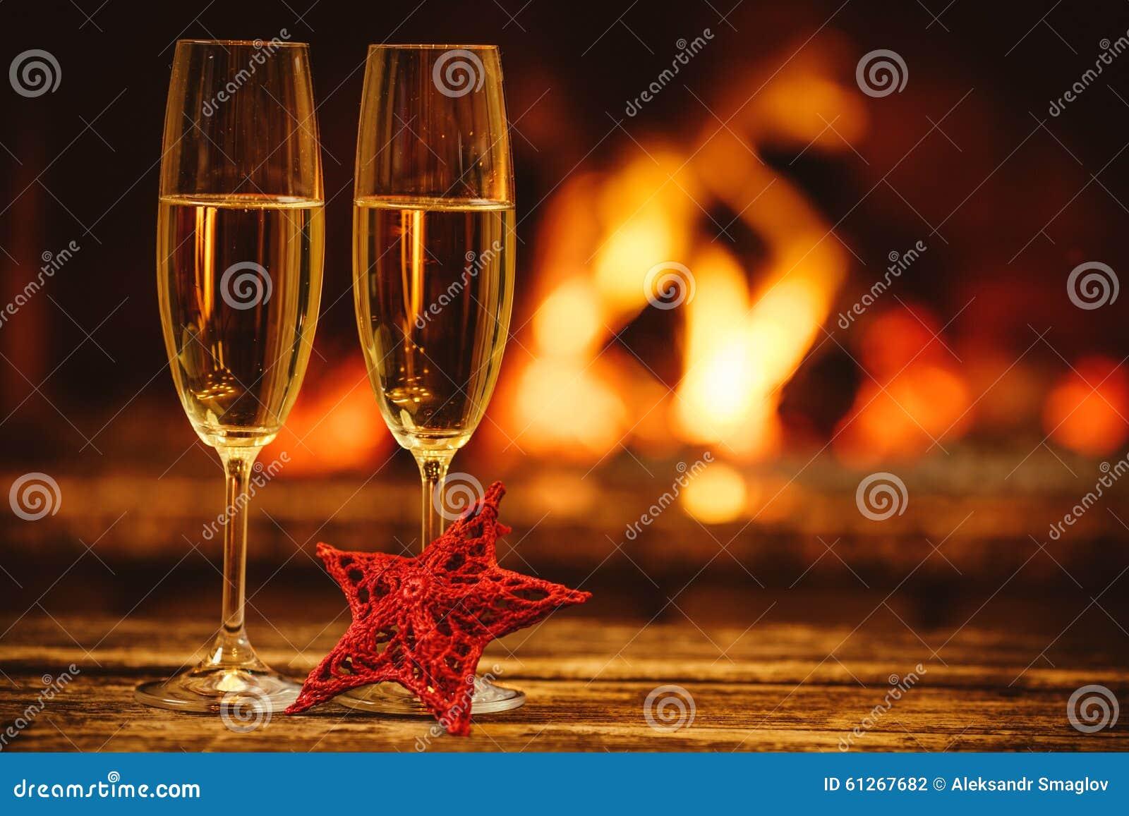 Två exponeringsglas av mousserande champagne framme av den varma spisen C