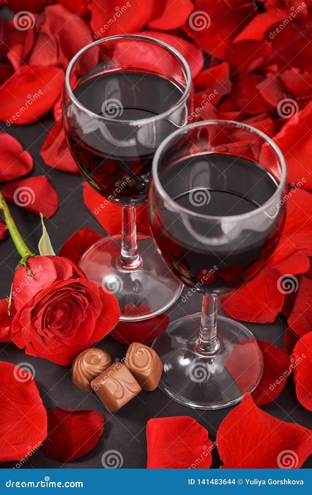 Två exponeringsglas av vin, ros, kronblad och choklader på en svart bakgrund