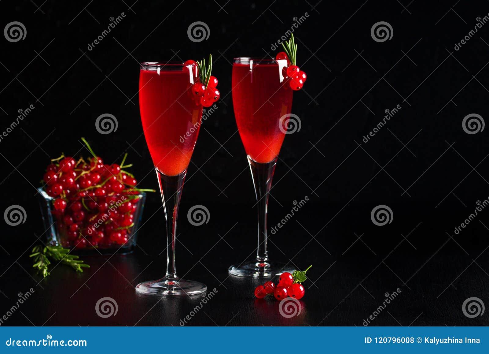Två exponeringsglas fruktsaft för redcurrantvindrink dekorerade med rosmarin