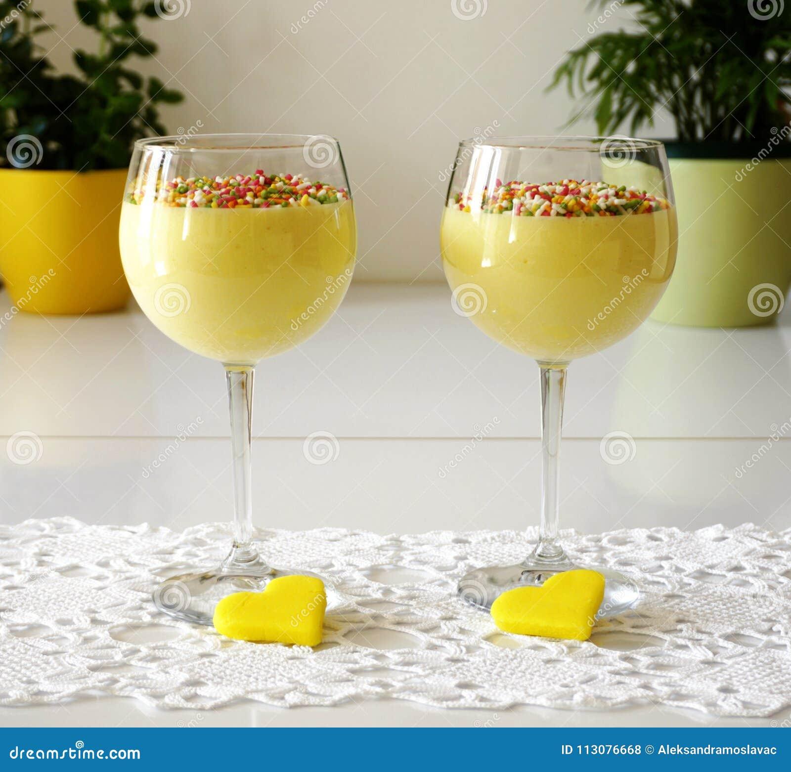 Två exponeringsglas med vaniljkräm dekorerade med kulöra stänk