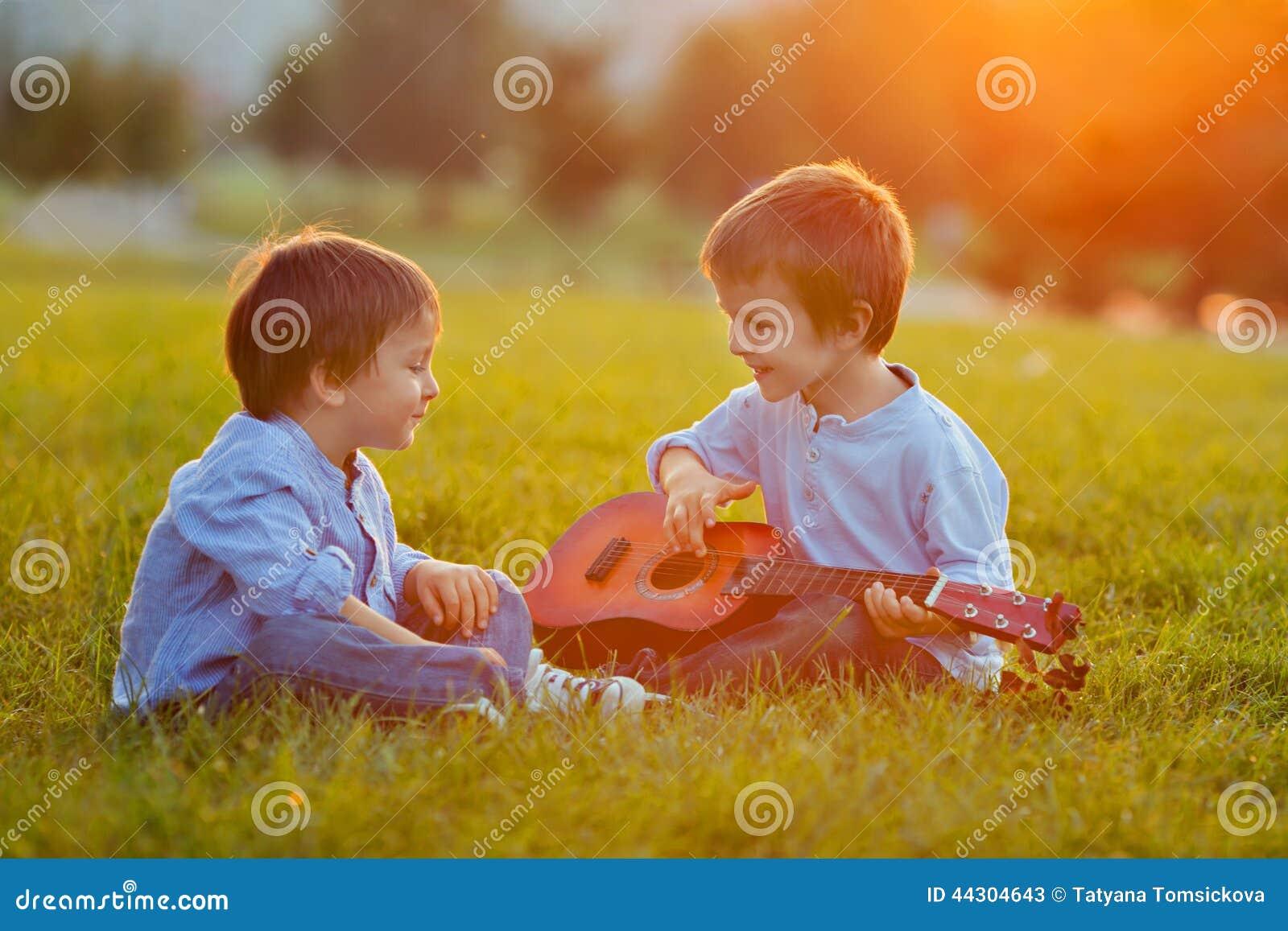 Två förtjusande pojkar och att sitta på gräset som spelar gitarren