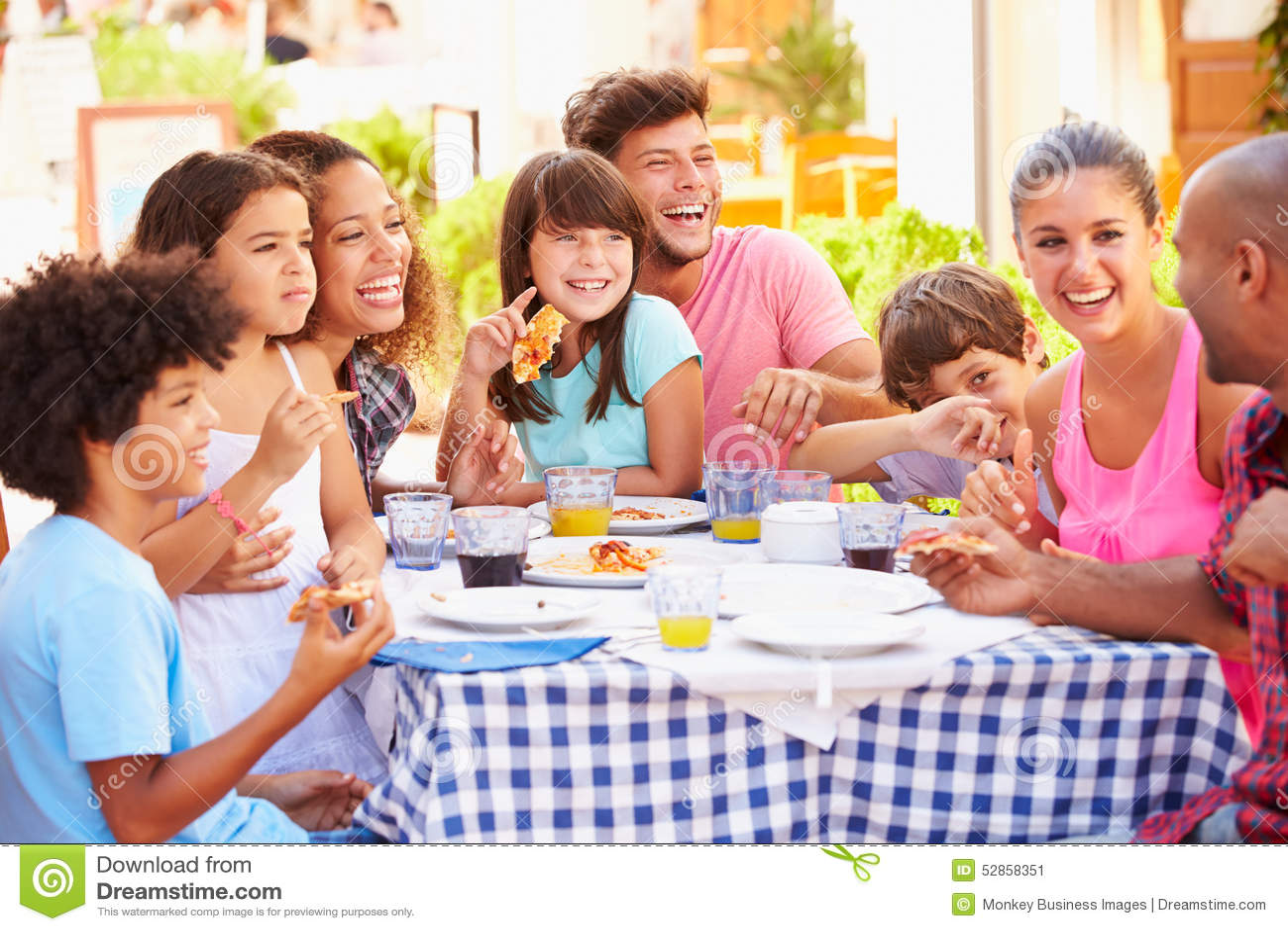 Två familjer som tillsammans äter mål på den utomhus- restaurangen